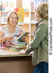 Librarian Scanning Books At Checkout Counter - Young boy...