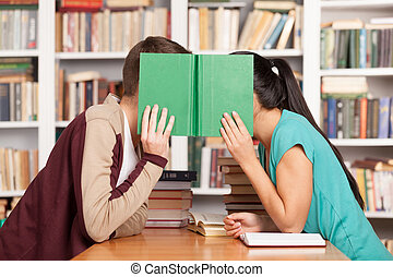 Library romance. Young man and woman sitting close to each...