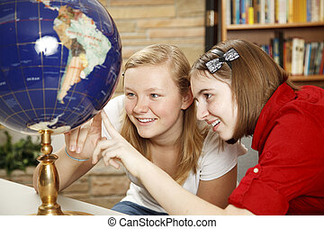 Library Teens Looking at Globe - Pretty teen girls in the...