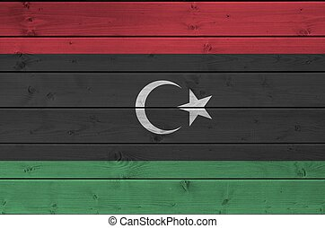 Libya flag depicted in bright paint colors on old wooden wall. Textured banner on rough background