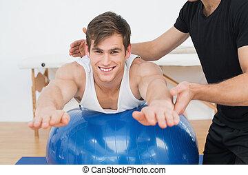 lichamelijke therapist, helpen, jonge man, met, yoga, bal