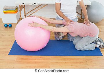 lichamelijke therapist, helpen, oude vrouw, met, yoga, bal