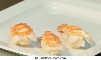 Lie down sushi with shrimp on a plate.