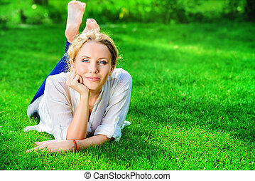 lie life - Beautiful happy woman lying on a grass outdoor...