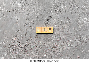 LIE word written on wood block. LIE text on cement table for your desing, concept