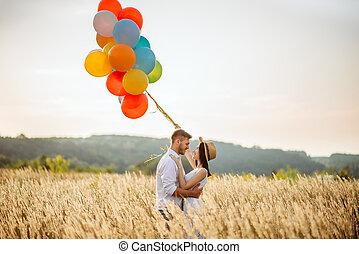 liebe, paar, mit, farbenprächtige luftballons, in, a, roggen, feld