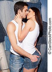 liebe, und, passion., schöne , junges, in, tank übersteigt, und, jeans, küssende , während, stehende , gegen, jeans, hintergrund