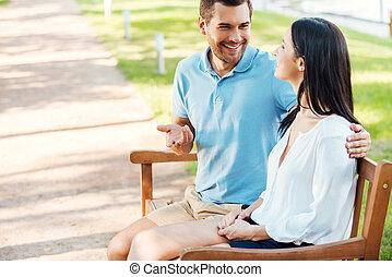 liebenden, in, park., seitenansicht, von, heiter, junger, liebenden, sitzen, bank, zusammen, und, sprechende