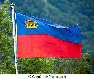 Liechtenstein flag in background of green trees and ...