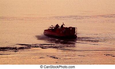 life boat patrol - a life boat patrols the water at sunset...
