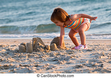 A baby-girl on a beach down-under working on a sandcastle