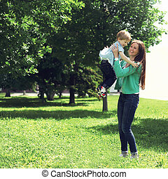 Life moment of happy family! Mother and son child playing having fun together outdoors at the weekend on the grass in sunny summer day