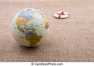 Life preserver beside a globe on canvas