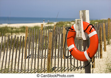 Life preserver on beach. - Life preserver hanging on post on...