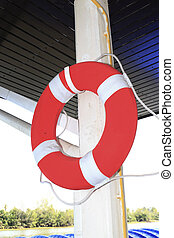 Life ring hang on white pole is on boat.