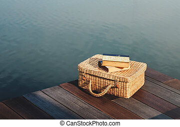 Life Unpluged Concept. Reading Book by the River. Holidays Leisure and Relaxing Lifestyle. Vintage Props on Wooden Patio Deck