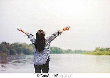 Life Unpluged. Happy Woman Standing by the River. Raising Arms to Breathing Fresh Air. Holidays Leisure and Relaxing Lifestyle