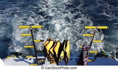 Life vest on ladders on the rear deck of yacht moving in the sea