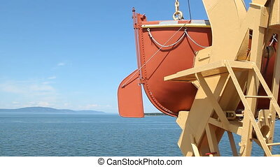 Lifeboat and rudder. - Detail of orange lifeboat on a ferry....