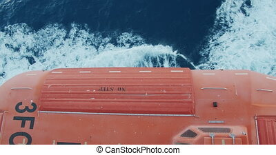 Lifeboats on deck of cruise liner with view on sea.
