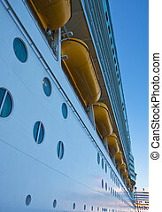 The side of a cruise ship with lifeboats and portholes