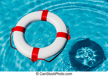 lifebuoy in a swimming pool - an emergency tire floating in ...