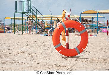 Lifebuoy on a beach sand summer sunny day