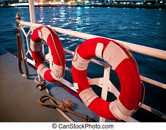 lifesavers on boat two red and white lifesavers on deck of large boat