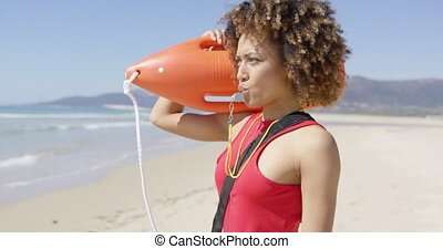 Lifeguard with rescue float blowing whistle and pointing with finger into distance. Tarifa beach. Provincia Cadiz. Spain.