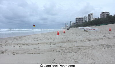 Lifeguard flag on sunny Gold Coast beach with Surfers Paradise in the background, Australia.