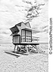 Lifeguard house on sand beach in miami, usa. Tower for rescue baywatch in typical art deco style. Wooden house on ocean shore on cloudy sky. Summer vacation concept. Public guarding and safety