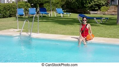 Lifeguard in red swimsuit sitting at edge of pool - Single...