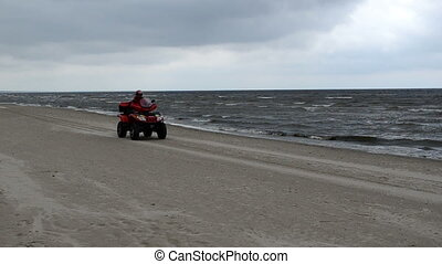 Lifeguard patrol quad bike motorcycle go near Jurmala beach seaside sea on circa August 2012 in Jurmala.