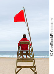 Lifeguard sitting in his chair watching the sea