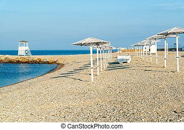 Lifeguard tower and beach umbrellas on the seashore in Nebug, Krasnodar Territory.