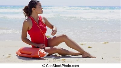 Seated young female lifeguard in red swimsuit with whistle buoy and hand near brow looking for rescues