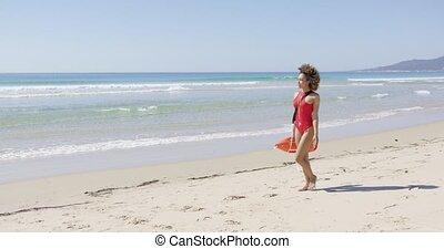 Lifeguard with rescue float walking along beach - Lifeguard...