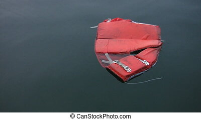 Lifejacket. 2 shots. - An abandoned lifejacket floats in the...
