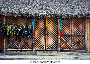 Lifejackets hang at the entrance to the store. The facade of the wooden structure