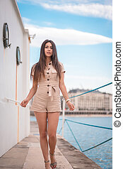 Lifestyle, a dark-haired Caucasian woman strolling in a brown suit on a boat