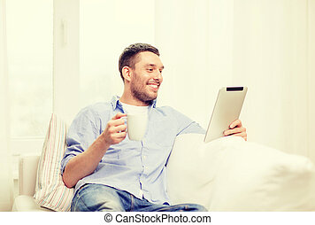 smiling man working with tablet pc at home