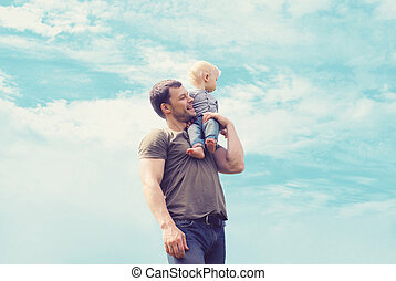 Lifestyle atmospheric portrait happy father and son having fun outdoors against blue sky with clouds, soft vintage pastel colors