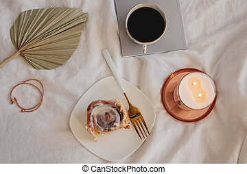Lifestyle composition with cinnamon bun, coffee and burning candle on the bed.