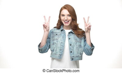 Lifestyle Concept: Happy redheaded girl in denim showing...