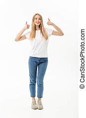 Lifestyle Concept: Happy smiling young woman in jeans looking at the camera giving a double thumbs up of success and approval isolated on white