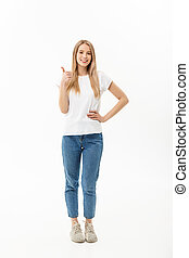 Lifestyle Concept: Happy smiling young woman in jeans looking at the camera giving a thumbs up of success and approval isolated on white