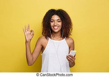 Lifestyle Concept - Portrait of beautiful African American woman joyful listening to music on mobile phone and show ok sign with fingers. Yellow pastel studio background. Copy Space.