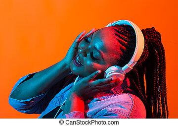 Lifestyle concept - Portrait of beautiful African American woman joyful listening to music.