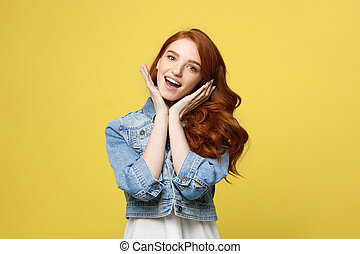 Lifestyle Concept: Smiling beautiful young woman in jean clothes posing with hands on chin. Isolated over yellow background.