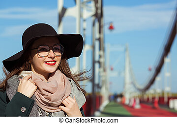 Lifestyle fashion portrait of beautiful brunette model walking at the city, wearing trendy outfit